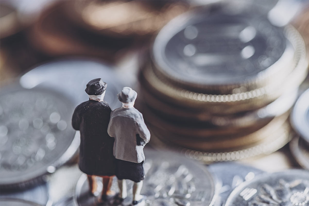 model of two elderly people on a stack of coins