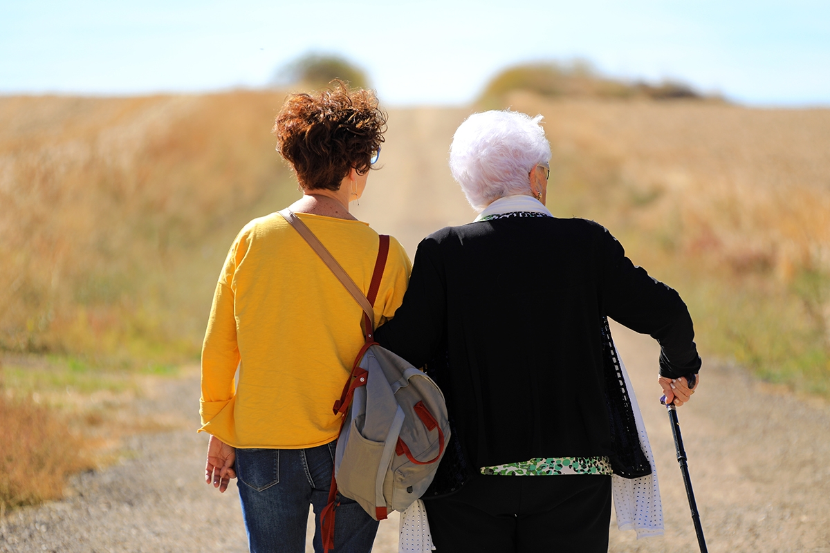 Female carer with elderly paerson taking a walk